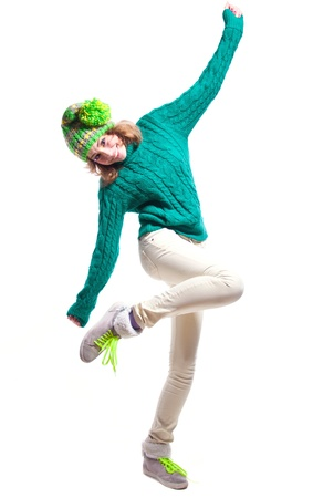 Cute winter girl wearing warm woolen knitted sweater, yellow green bright hat with pompon, light yellow pants, boots with green laces, colorful makeup, dancing, having fun, looking at camera with toothy smile. Isolated on white