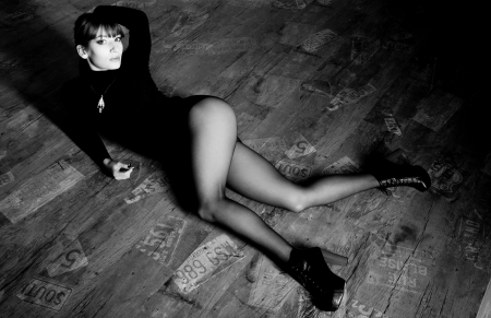 Studio full length portrait of young beautiful brunette woman model wearing black jumper, shorts, tights, black leather shoes with red high heels, lying on the floor, looking at camera photo