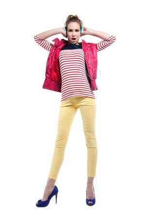 Pretty young girl isolated on white wearing bright casual clothes like yellow pants, stripped red white and blue shirt, pink vest, purple high heels, listening to music, holding headphones with hands, dancing, mouth open, looking at camera Stock Photo - 21548341