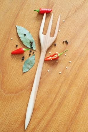 Kitchen still life made of wooden fork, red chili peppers cut and in whole, black pepper, bay leaves with wooden spoon on the wooden texture table background. Top view photo