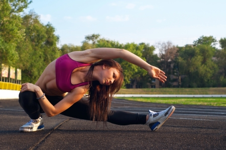 Pretty sporty brawny strong, slim and fit young woman sitting, doing split and stretching exercises, stretching out to reach her foot. At the stadium, on running tracks. During sunset. Green trees at background