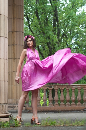 Beautiful young woman model wearing pink violet silk tunic dress, moving aside, wind blowing up her dress high so that slim long legs can be see. Near columns photo
