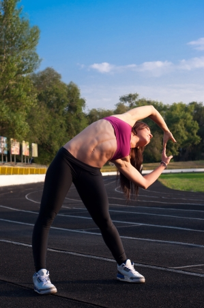 Pretty sporty brawny strong, slim and fit young woman standing, doing split and stretching exercises, bending aside, all abdomen muscles showing wel, At the stadium, on running tracks during sunset photo