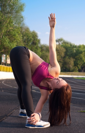 Pretty sporty brawny strong, slim and fit young woman standing, bending down, doing stretching exercises, holding one of her legs with the hand, another hand up. At the stadium, on running tracks during sunset photo