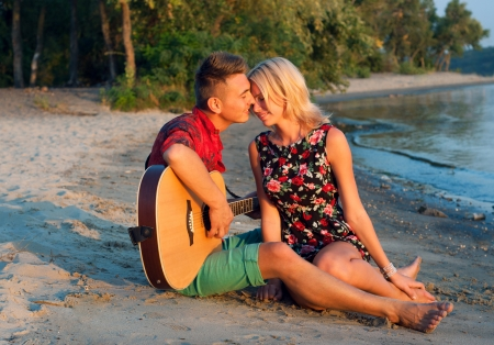 Young pretty couple of man and woman in love sitting on the beach close to each other, man playing the guitar, both smiling, feeling happy together. During sunset photo