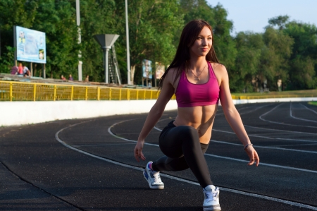 Pretty sporty strong slim and fit young woman athelete doing stretching exercises, standing on low start, looking forward and smiling. At the stadium, on running tracks Stock Photo
