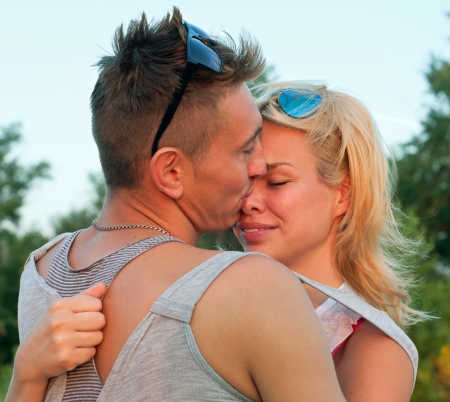 Young pretty couple of man and woman wearing tees and sunglasses, being in love close to each other, embracing, kissing, feeling happy together. At sunset. Main focus on girl photo