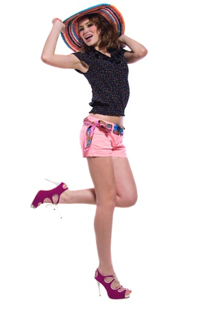 Young beautiful woman model wearing colorful wicker hat, top, shorts, pink high heels, standing, dancing, having fun, holding her hat with hand, looking at camera. Isolated on white, copy space photo