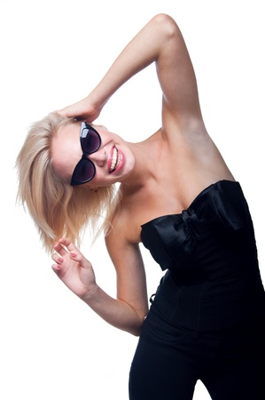 Funny beautiful young blond woman model wearing stylish black top with big silk bow, black trausers and sun glasses, bright pink lipstick, having fun, dancing, looking at camera. Isolated on white photo