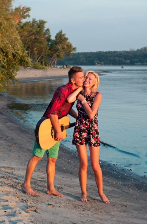 Young pretty couple of man and woman in love on the beach close to each other, man playing the guitar, both smiling, laughing, kissing, feeling happy together. During sunset photo
