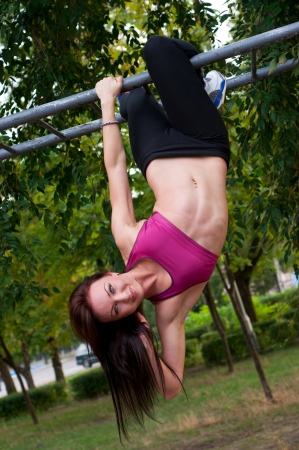 Pretty sporty strong slim and fit young woman hanging down from a horizontal bar, holding with one hand, doing exercises. Green trees at background photo