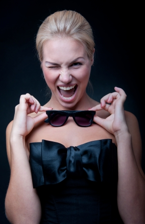 Funny beautiful young blond woman model wearing stylish black top with big silk bow, bright pink lipstick, holding sun glasses in her hands, having fun, laughing, shouting, smiling with toothy smile, looking at camera. Black background photo