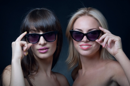 Studio portrait of two young beautiful women models wearing sun glasses, smiling and looking at camera. Black background photo