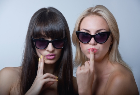 Studio portrait of two cute beautiful young women models wearing sun glasses, holding hands near lips and chin Stock Photo