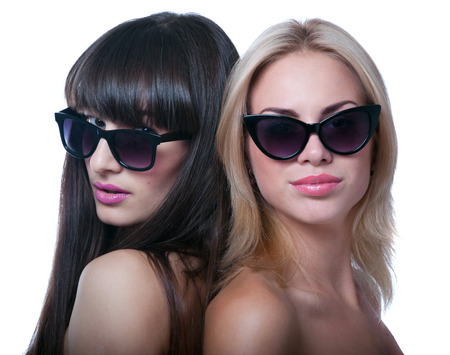 Studio portrait of two young beautiful women models wearing sun glasses photo