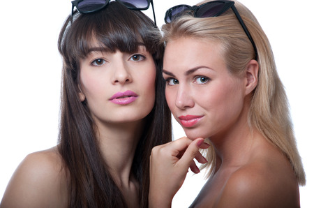 Studio portrait of two young beautiful women models wearing sun glasses Stock Photo - 22248576