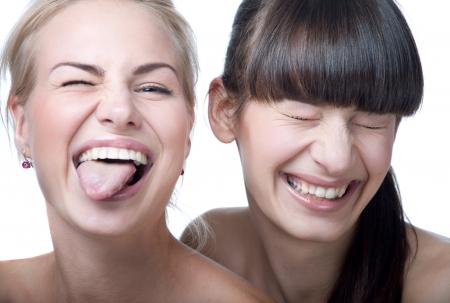 Close-up studio portret van twee jonge mooie grappige en schattige meisjes gek, spelen apen, maken van gezichten in de voorkant van een camera. Kijken naar de camera. Geïsoleerd op witte achtergrond Stockfoto