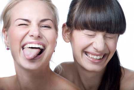Nahaufnahmestudioportrait von zwei jungen schönen lustigen und niedlichen Mädchen verrückt, spielen Affen machen Gesichter vor einer Kamera. Blick in die Kamera. Isoliert auf weißem Hintergrund
