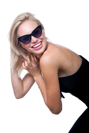 Funny young woman model in stylish black top and jeans, sun glasses, bright pink lipstick, having fun, laughing, ruffling disheveled hair, smiling, looking with toothy smile at camera. Isolated on white