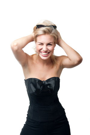 Funny young woman model in stylish black top with big silk bow, sun glasses on forehead, bright pink lipstick, having fun, laughing, ruffling disheveled hair, winking, smiling, looking with toothy smile at camera. Isolated on white