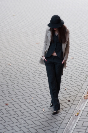 Pretty brunette woman model wearing stylish black pants suit and gray rain coat, black hat with wide fields, high heels, red lips, hands in pockets, going down the street covered with pavement tiles  Copy space photo