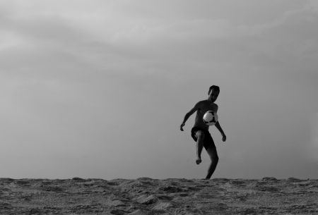Black and white silhouette photograph of a young man playing soccer, kicking the ball on the sandy beach  Copy space  photo
