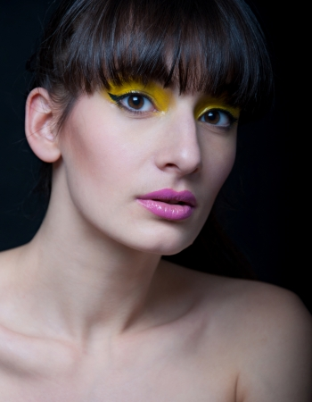 Studio portrait of young pretty woman model with bright yellow makeup, wearing pink lipstick, hair pulled back, looking at camera  Black background Stock Photo