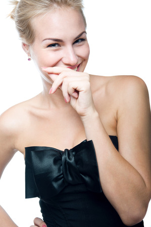 Pretty blond woman with clean face, hair pulled back, laughing happily, covering her laughter with her hand, wearing black silk top with big bow  Isolated on white photo