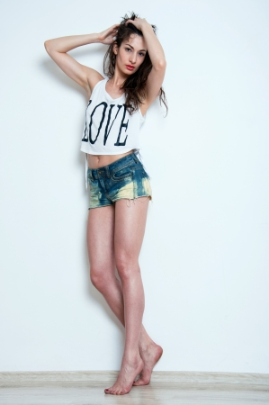 Pretty sexy woman model with amazing body, beautiful long legs, standing on tiptoes, holding hair with hands, wearing blue denim shorts, white top with black love print, looking at camera  Light gray background, copy space photo
