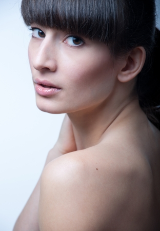 Studio portrait of beautiful brunette woman model with straight long fringe, brunette hair pulled back, with clean face and natural makeup over grey background