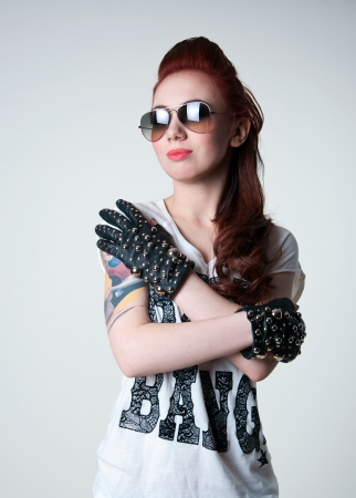 Pretty rocker woman model with cute red haircut, wearing black leather gloves with spikes, white top, glasses, looking aside  Gray background, copy space photo
