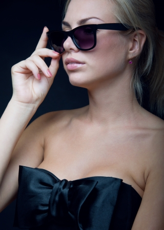 Pretty young blond woman model wearing stylish black top with big silk bow, sun glasses, bright pink lipstick, looking to the side  Black background, copy space
