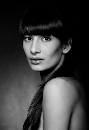 Black and white studio portrait of pretty young brunette woman model with bare shoulders, long hair, straight fringe, natural makeup, glossy lips lightly open, looking at camera