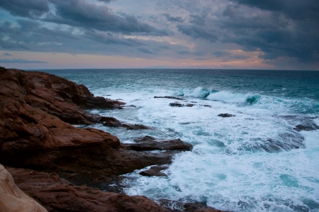 Stormy blue Ligurian sea with white spumy waves crashing against brown rocks  During sunset in autumn