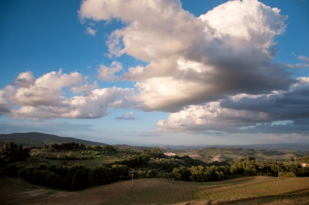 Typical Italian rural landscape with a farm house on the horizon, bright blue sky and white clouds Stock Photo