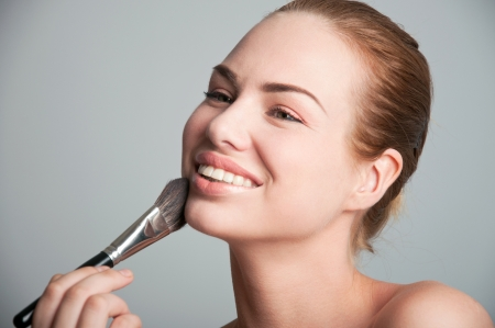 Studio portrait on gray of a young happy pretty woman model wearing natural makeup, applying powder to her skin with a special brush, looking at the brush, smiling with toothy smile. Copy space