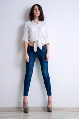 Studio test shot of pretty young brunette woman model with very long slim legs wearing blue jeans, white shirt, beige high heels, standing still, looking at camera. Over light gray background photo