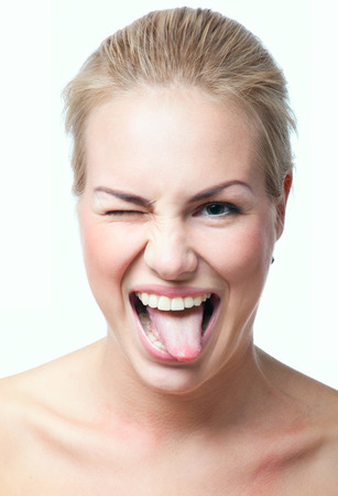 Funny cute blond woman making faces, showing her tongue, winking, looking at camera. Isolated on white