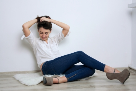 Pretty brunette woman wearing blue jeans, white shirt, sitting on the floor in a minimalistic room against white wall, looking down, holding hair with arms, smiling. Copy space