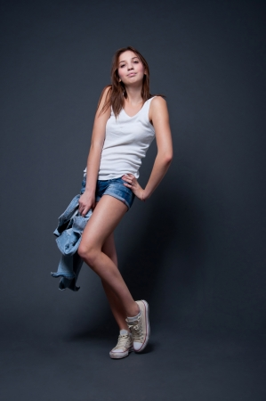 short shorts: Cute and funny pretty young girl with very long legs wearing white top, blue denim shorts, sneakers, holding a jacket in her hands, standing, dancing and smiling. In studio over gray background
