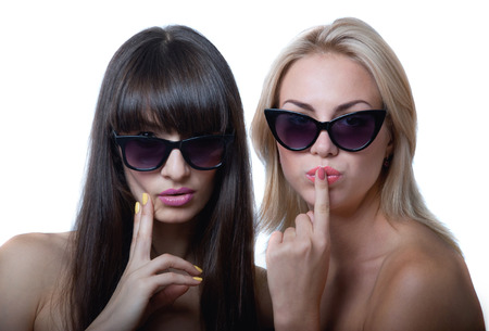 Studio portrait of two cute beautiful young women models wearing sun glasses, holding hands near lips and chin, smiling and looking at camera. Isolated on white background