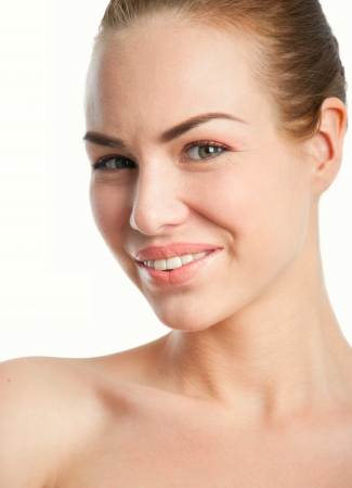 Studio closeup portrait of young pretty woman model wearing tender natural makeup, hair pulled back, looking at camera and smiling with toothy smile. Isolated on white background