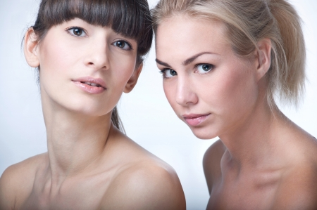 Studio portrait of two young beautiful women models on gray background