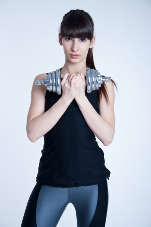 Pretty young slim and fit brunette woman trainer holding a  heavy metal dumbbell, doing workout, training her muscles to become strong. Lookingat camera. In studio over gray background photo