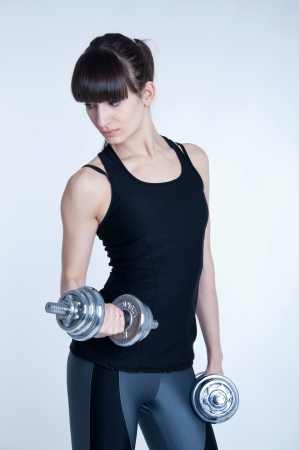 Pretty young slim and fit brunette woman trainer doing workout with heavy metal dumbbells, training her muscles to become strong. In studio over gray background photo