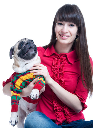 Pretty young brunette girl in jeans and pink blouse, sitting on the floor, holding and embracing her pug dog pet in warm knitted winter sweater, looking at camera, smiling ith toothy smile. Isolated on white background photo