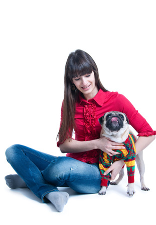 Pretty young brunette girl wearing jeans and pink blouse, sitting on the floor, playing and holding her pug dog pet in warm knitted winter sweater, a dog licking its nose. Isolated on white background photo