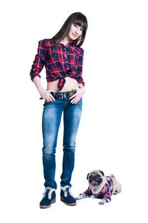 Pretty young brunette woman model with long straight hair, standing together with her friend pug dog pet, both wearing squared pattern shirts, girl wearing jeans and cool winter shoes. Isolated on white photo