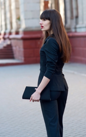 Outdoors profile portrait of successful young attractive business woman wearing a smart black suit, bright red lipstick, holding an elegant clutch bag in  her hand, walking somewhere, looking aside. Copy space photo