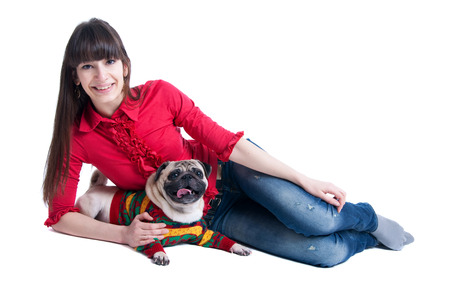 Pretty young brunette girl wearing jeans and pink blouse, lying on the floor together with her pug dog pet in warm knitted winter sweater, a dog showing its tongue, both smiling at camera. Isolated on white background photo